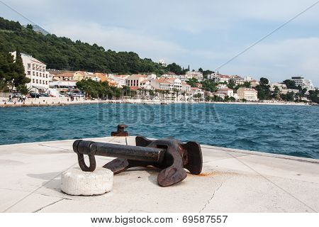 Old rusty ship anchor in the harbor in Podgora, Croatia
