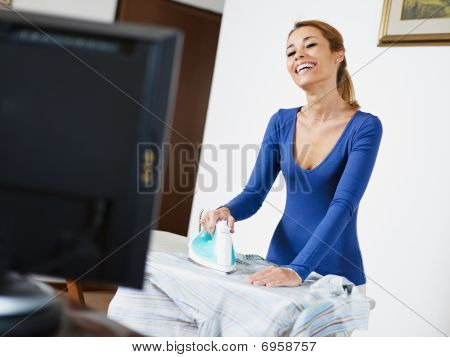 Woman Ironing Shirt While Watching Television