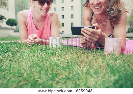 Two Young Women Laughing On The Grass