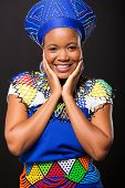 stock photo of zulu  - portrait of happy zulu woman on black background - JPG