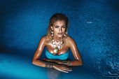 image of skinny girl  - Portrait of beautiful blonde woman relaxing in blue water looking at camera - JPG