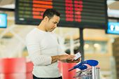 picture of boarding pass  - handsome man looking at boarding pass in front flight information board at airport - JPG