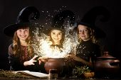 stock photo of witches  - Three little Halloween witches reading spell above pot - JPG