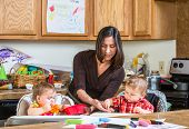 stock photo of babysitter  - A mother in the kitchen feeds babies breakfast - JPG