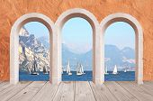 stock photo of arcade  - beautiful arcade vintage wall mediterranean style with lake view to sail boats and mountains - JPG