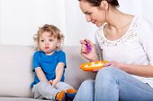 picture of fussy  - Young woman feeding her fussy child while sitting on a sofa - JPG