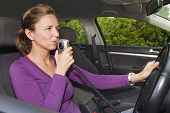image of sobriety  - Young woman in car blowing into breathalyzer - JPG