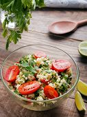 foto of tabouleh  - Tabbouleh with couscous and parsley healthy salad in glass bowl on wooden table - JPG