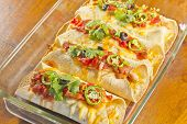 stock photo of mexican  - Delicious home made Mexican enchiladas in a casserole dish - JPG