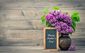 stock photo of vase flowers  - bouquet of lilac flowers in vase on wooden background - JPG