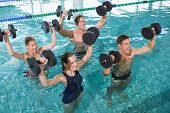 image of day care center  - Happy fitness class doing aqua aerobics with foam dumbbells in swimming pool at the leisure centre - JPG