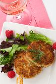 pic of crab-cakes  - Two crab cakes appetizer garnished with spicy sauce green salad and raspbery - JPG
