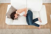 stock photo of hormone  - High angle view of young woman suffering from stomachache on sofa at home - JPG