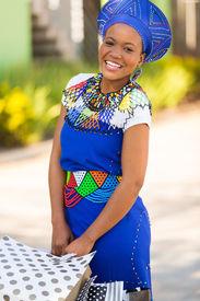stock photo of zulu  - happy african zulu woman with shopping bags in mall - JPG