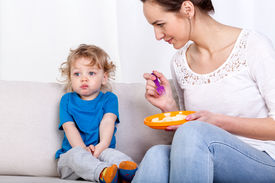 stock photo of fussy  - Young woman feeding her fussy child while sitting on a sofa - JPG