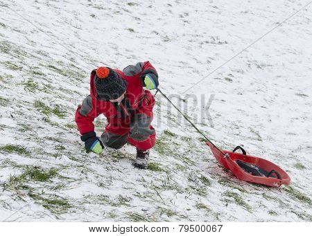 Child Pulling Sledge Up Hill