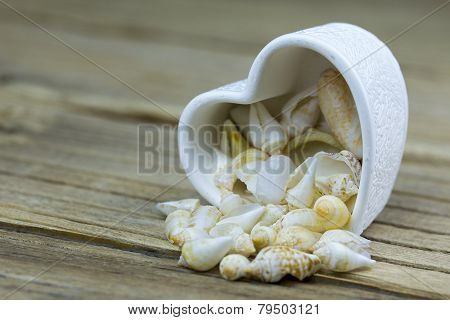 Shape Of Heart Made With Shells On A Wooden Table