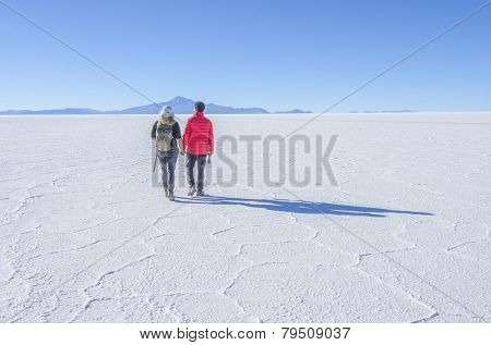 Couple of tourists walking at Salar de Uyuni, Bolivia