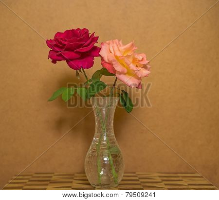 Two Roses In A Vase Against Grunge Background