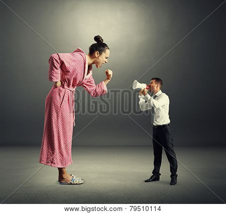 angry big woman screaming and showing fist to small man with megaphone over dark background