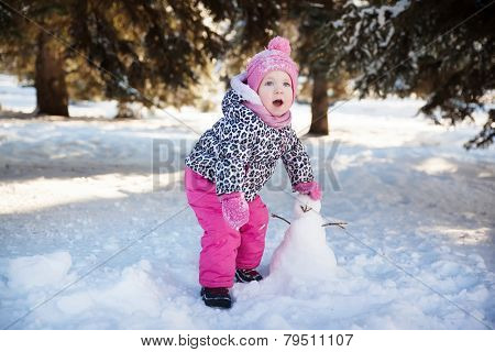 little girl playing with a snowman