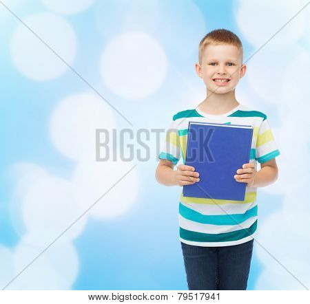 education, childhood and school concept - smiling little student boy with book over blue background