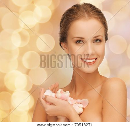 beauty, people and health concept - beautiful smiling young woman with flowers and bare shoulders over beige lights background
