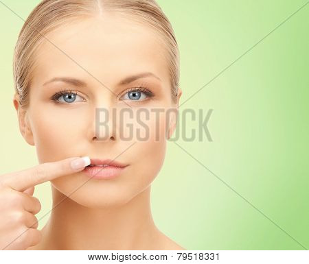 beauty, people and health concept - beautiful young woman pointing finger to her lips over green background
