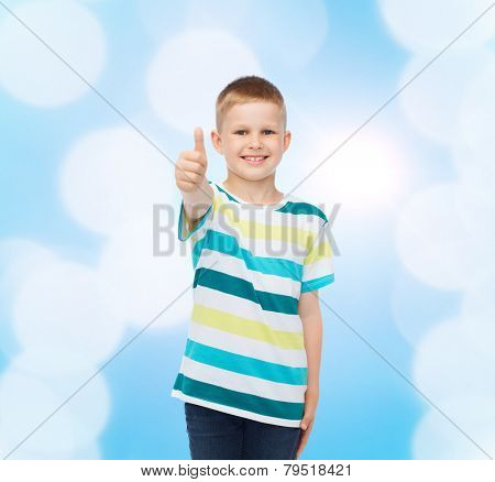 happiness, childhood and people concept - smiling little boy in casual clothes with showing thumbs up over blue background