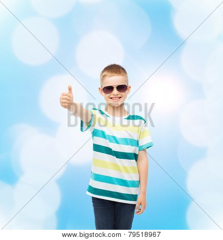 happiness, summer, childhood, gesture and people concept - smiling cute little boy in sunglasses over blue background showing thumbs up