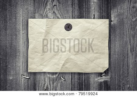 Empty Yellow Paper Ad Hanging On Gray Wooden Wall