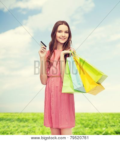 retail and sale concept - smiling woman in dress with many shopping bags and credit card