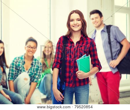 education and people concept - smiling female student with laptop bag and notebooks