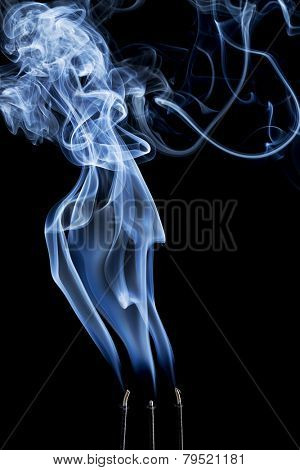 delicate smoke plume and swirls from  burning three incense sticks