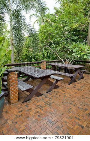 Wooden Chairs And Table Set At Balcony In A Green Plant Garden.