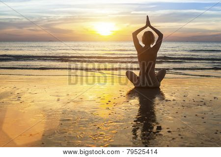 Woman doing meditation near the ocean. Yoga silhouette.