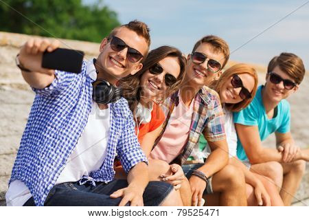 friendship, summer, technology and people concept - group of smiling friends with smartphone and headphones making selfie outdoors