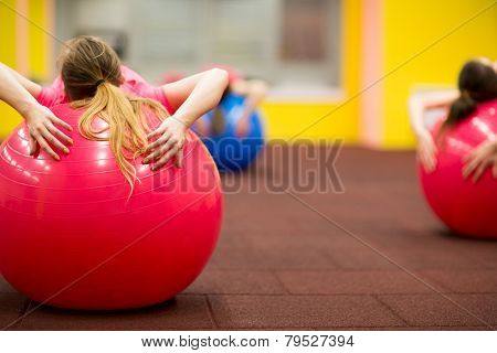 Group people in a pilates class at the gym - young woman with gymball at fitness training (shallow DOF, color toned image)
