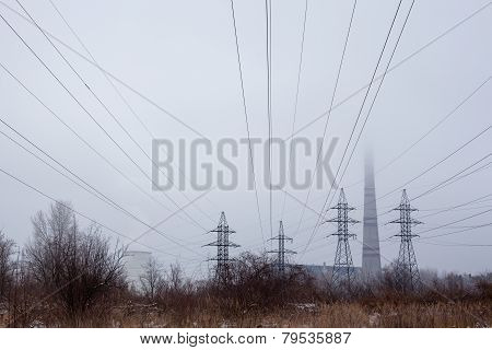 Electricity Pylons, Power Lines And Smoke Stack In Fog