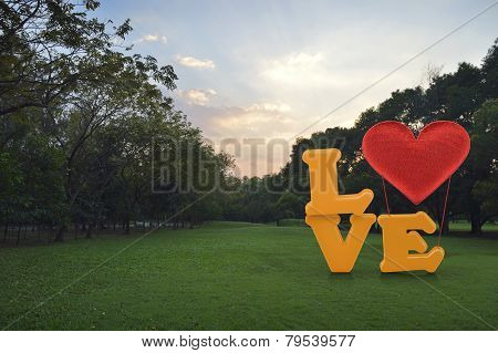 Love Word With Heart Shape Ballon On Green Grass In Park