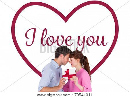 Loving couple holding a gift against valentines love hearts