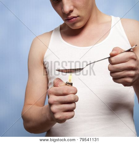 Man with a hardline drug addiction heating drugs in a spoon over a flame