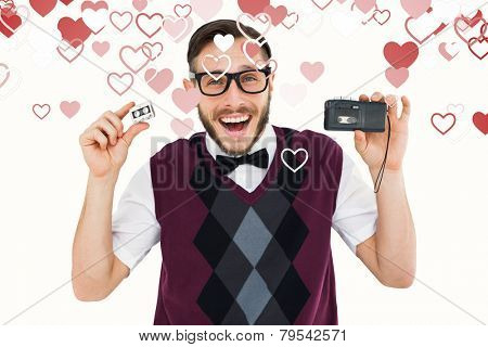 Geeky hipster holding a retro tape cassette player against valentines heart design