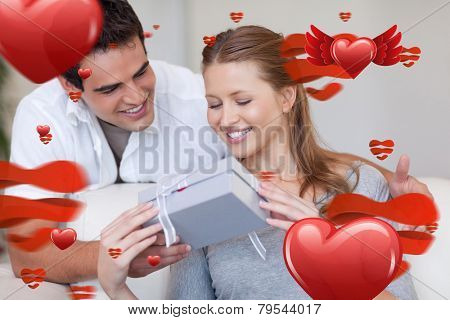Woman opening the gift she got from her boyfriend against love heart pattern
