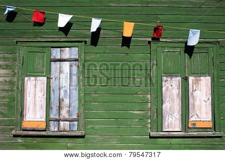 Green Wall Of An Old House With A Window And Choked Flags