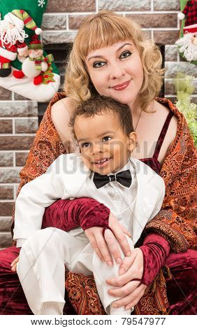 Happy Mother And Black Baby Boy Cuddling By Fireplace. Christmas And New Year