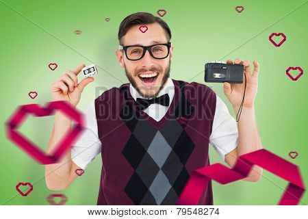 Geeky hipster holding a retro tape cassette player against green vignette