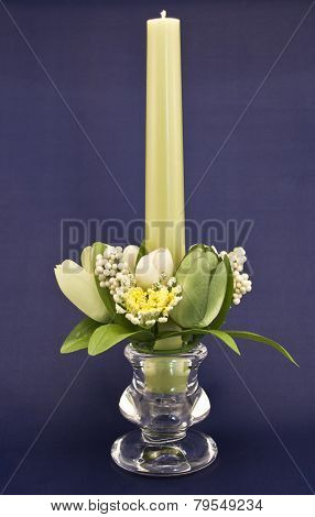 Candle holder with green pillar candle against blue background