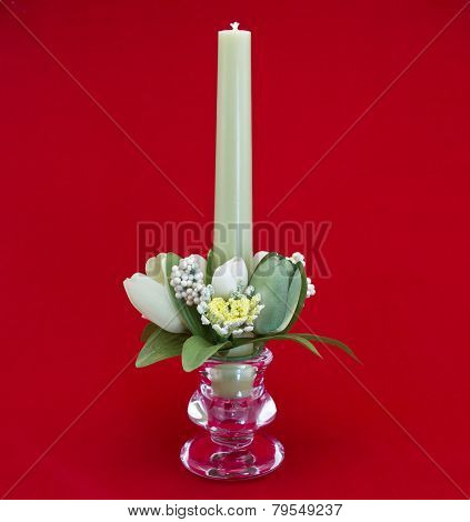 Candle holder with green pillar candle against red background