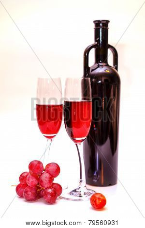 original red wine bottle, red grapes and two wine glasses on white